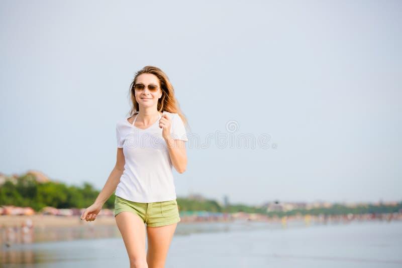 Молодая женщина caucasion бежать на пляже на стоковая фотография rf