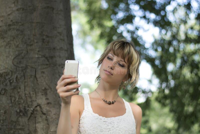 Молодая женщина outdoors принимая фото или selfie с ca сотового телефона стоковые фотографии rf