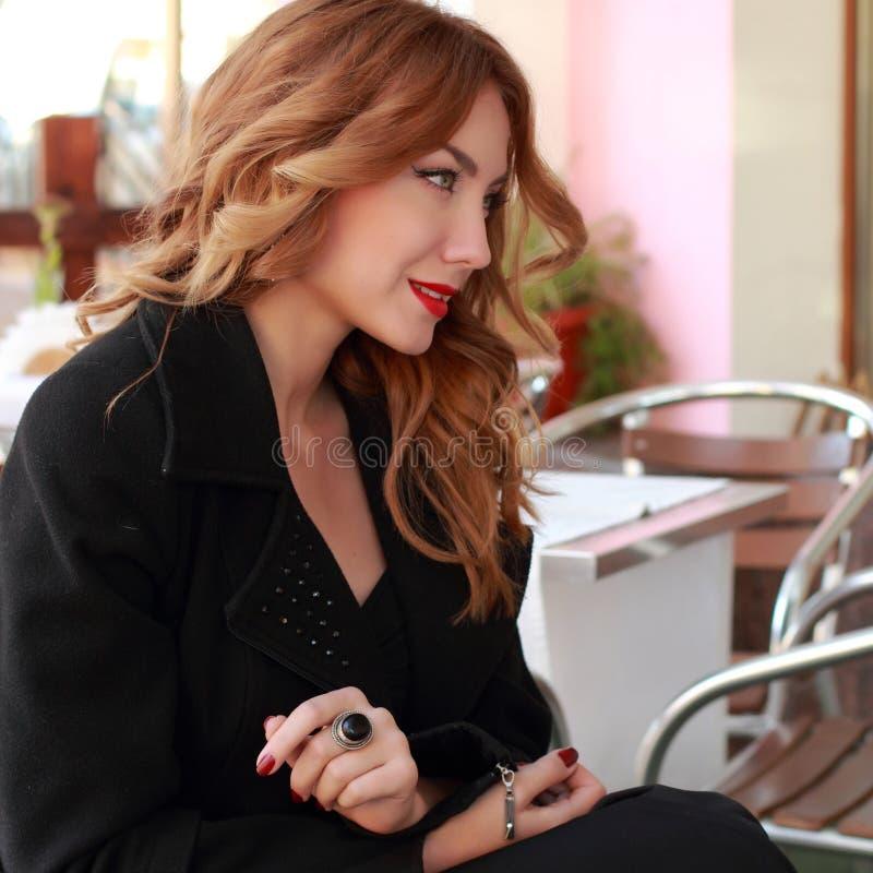 Молодая женщина Smiley привлекательная в кафе улицы стоковая фотография
