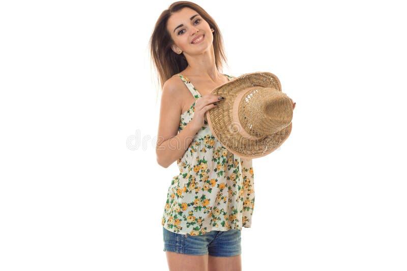 Молодая жизнерадостная девушка в sarafan при цветочный узор и соломенная шляпа смотря и усмехаясь на камере изолированной на бели стоковое изображение