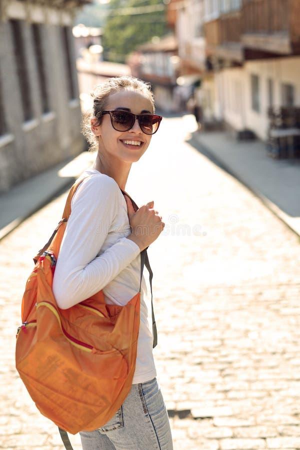 Молодая жизнерадостная женщина с малым оранжевым packpack стоковые фото