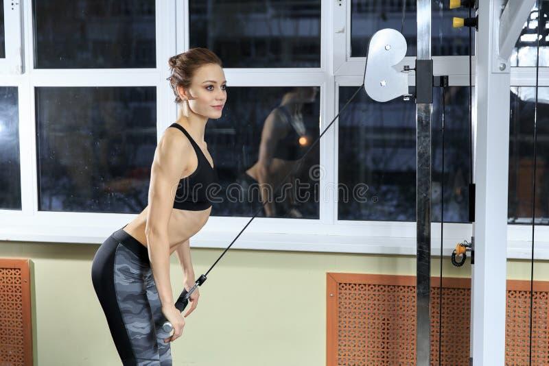 Молодая здоровая женщина фитнеса делая тяжеловесную тренировку для трицепса на машине в спортзале стоковое изображение