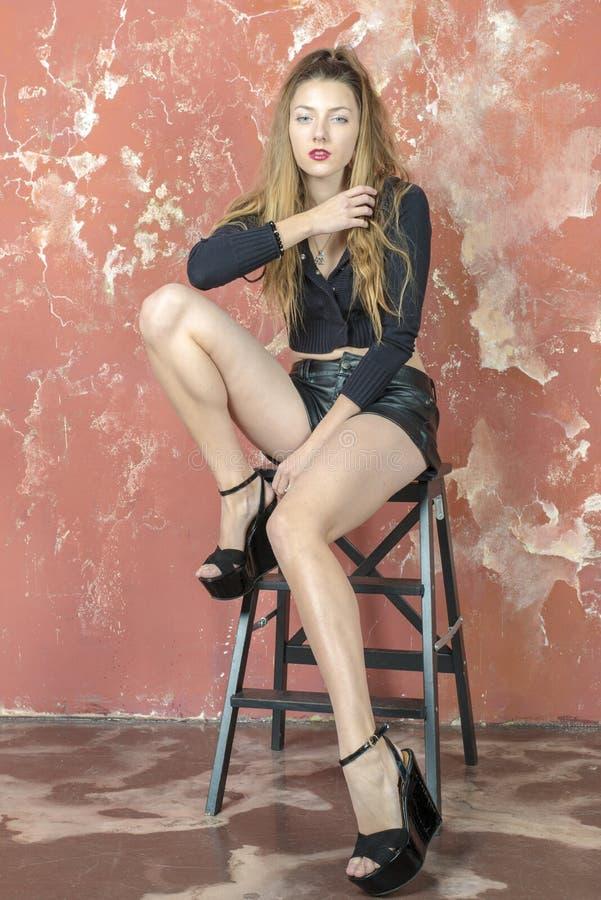 Молодая длинн-с волосами длинн-шагающая тощая девушка в шортах черного свитера и кожи и сандалиях платформы стоковые фото