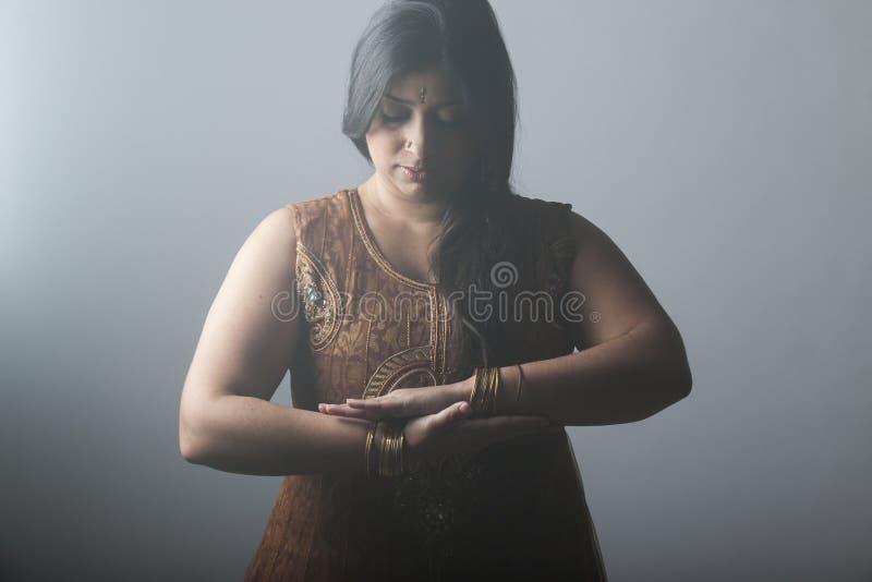 Молодая индийская женщина обнимая ее этничность стоковые изображения rf
