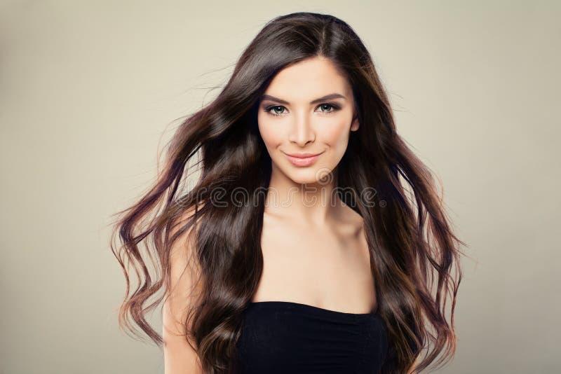 Молодая испанская женщина фотомодели с волосами Брайна дуя стоковое фото rf