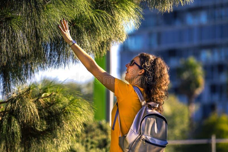 Молодая и курчавая женщина касается кроне дерева, видя ее в первый раз стоковые фотографии rf