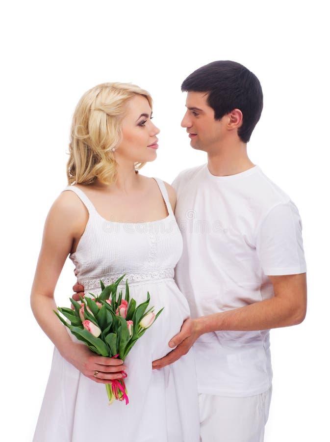 Молодая и симпатичная кавказская пара держа цветки стоковая фотография