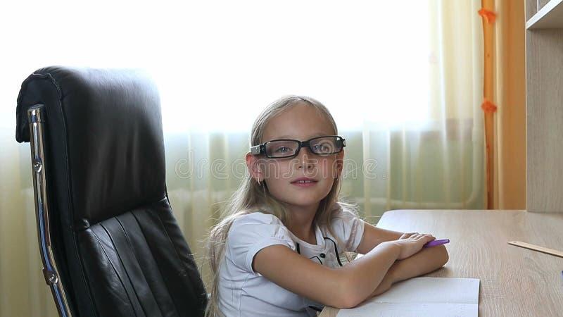 Молодая кавказская девушка в стеклах сидя на стуле таблицей Внутри помещения закройте вверх по взгляду на милой девушке в стеклах стоковые изображения rf