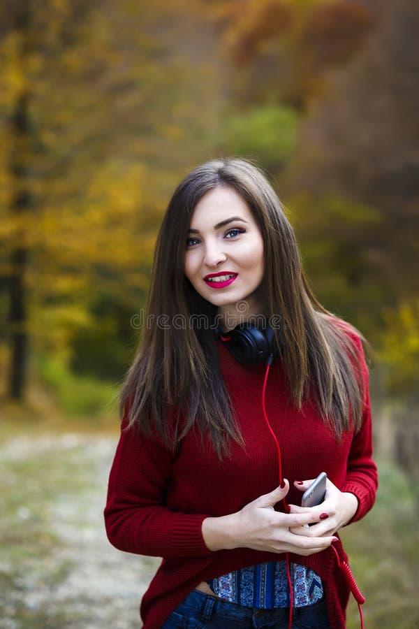 Молодая кавказская женщина брюнет с наушниками outdoors на autum стоковое изображение rf
