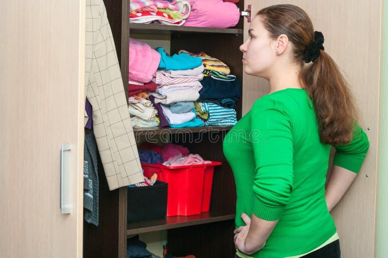 Молодая кавказская женщина в шкафе выбирая вещи стоковые изображения rf