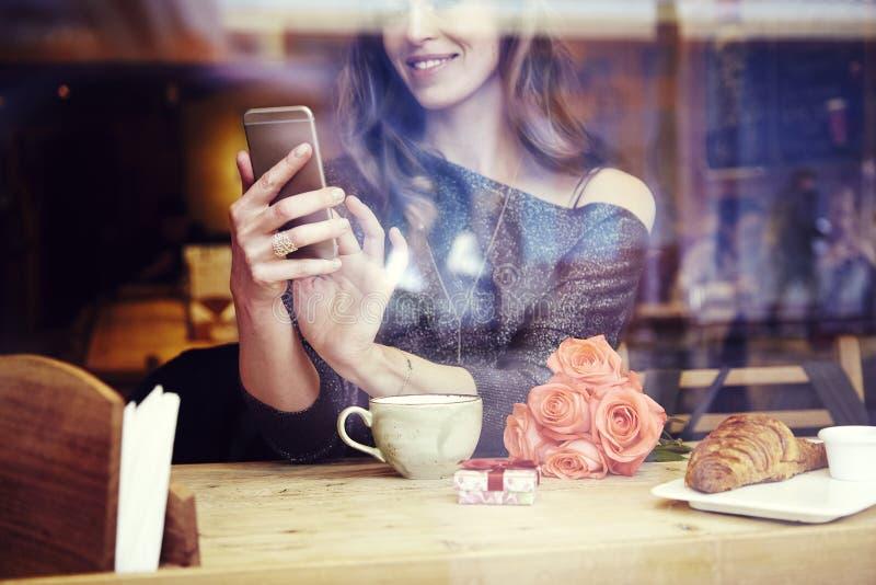 Молодая кавказская женщина при длинные волосы сидя около окна в кафе стоковые изображения rf