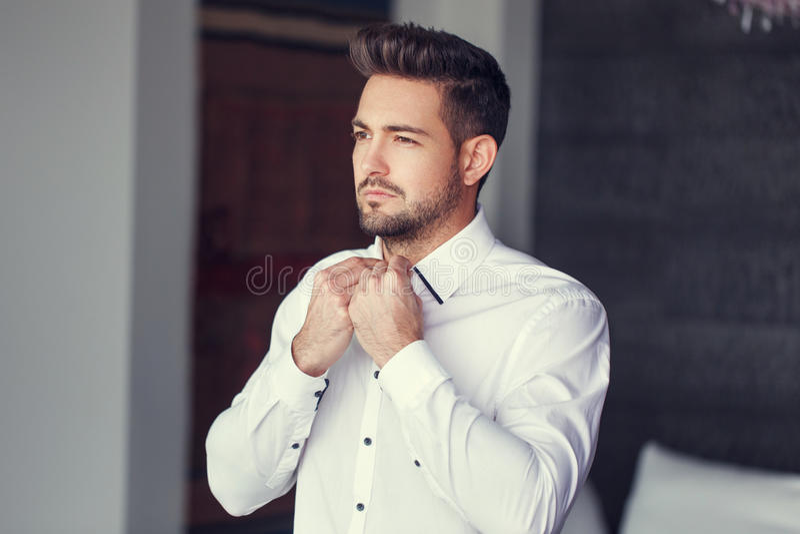 Молодая кавказская шлихта человека положила дальше рубашку стоковая фотография rf