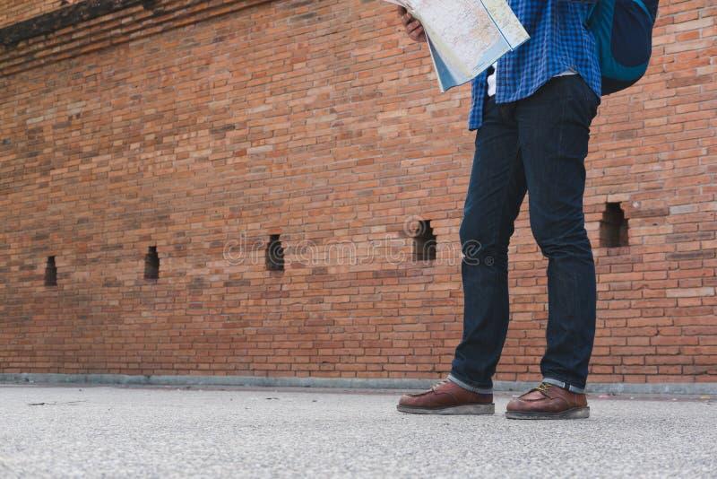 молодая карта чтения путешественника азиатский человек нося голубые рубашку и jea стоковое фото