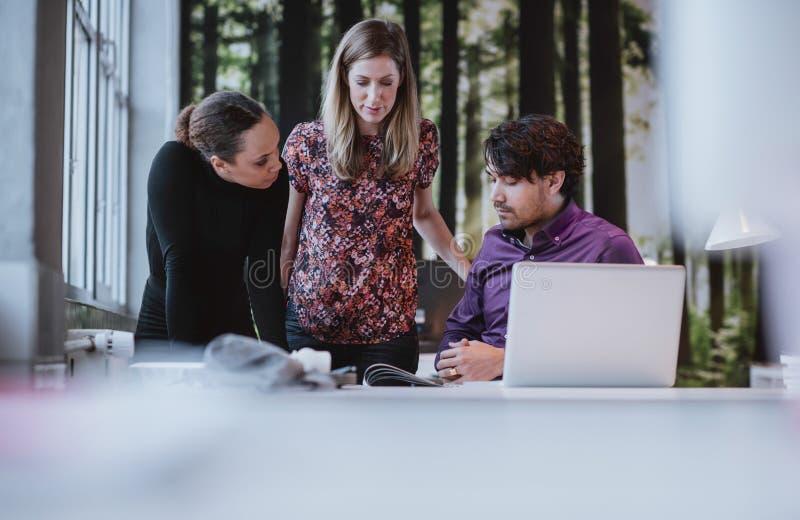 Молодая команда дизайнеров обсуждая издание кассеты стоковая фотография rf