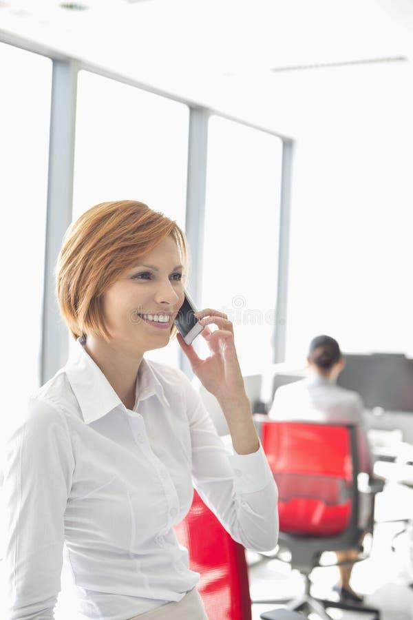 Молодая коммерсантка говоря на сотовом телефоне с коллегами в предпосылке на офисе стоковые изображения rf