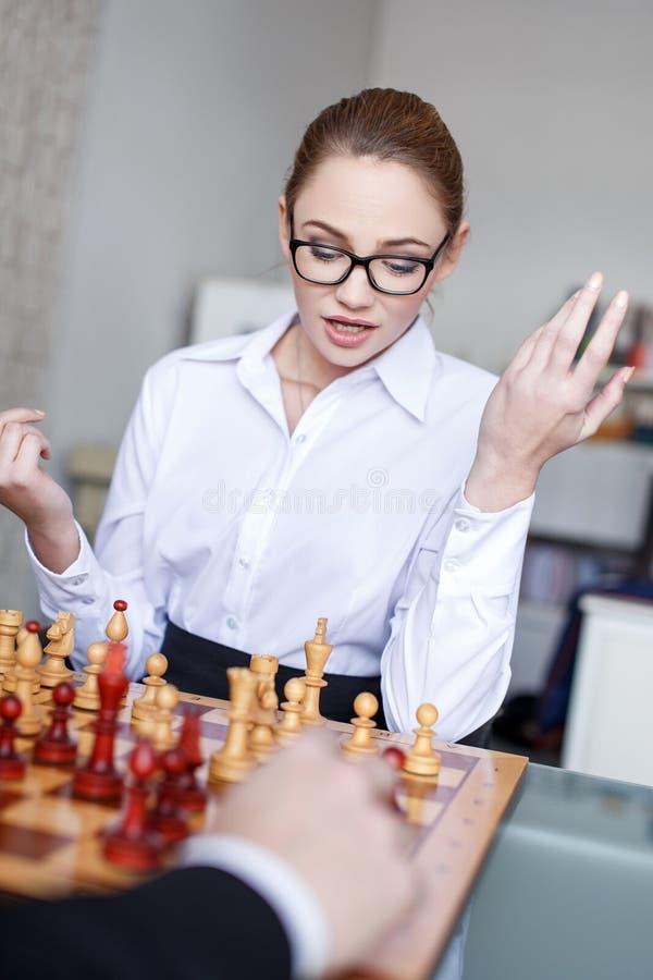 Молодая коммерсантка играя шахмат с бизнесменом стоковое фото rf