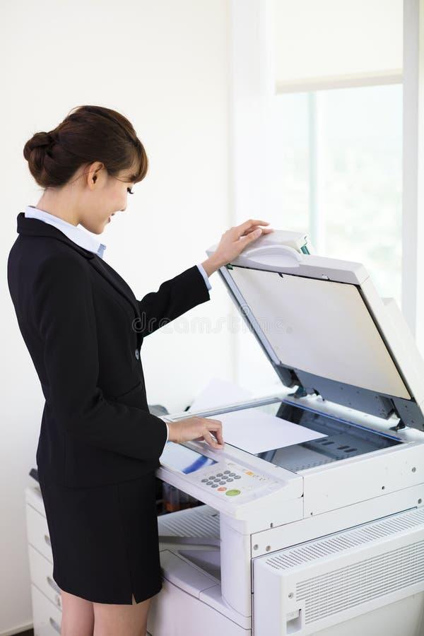 Молодая коммерсантка используя машину фотокопии стоковое фото rf