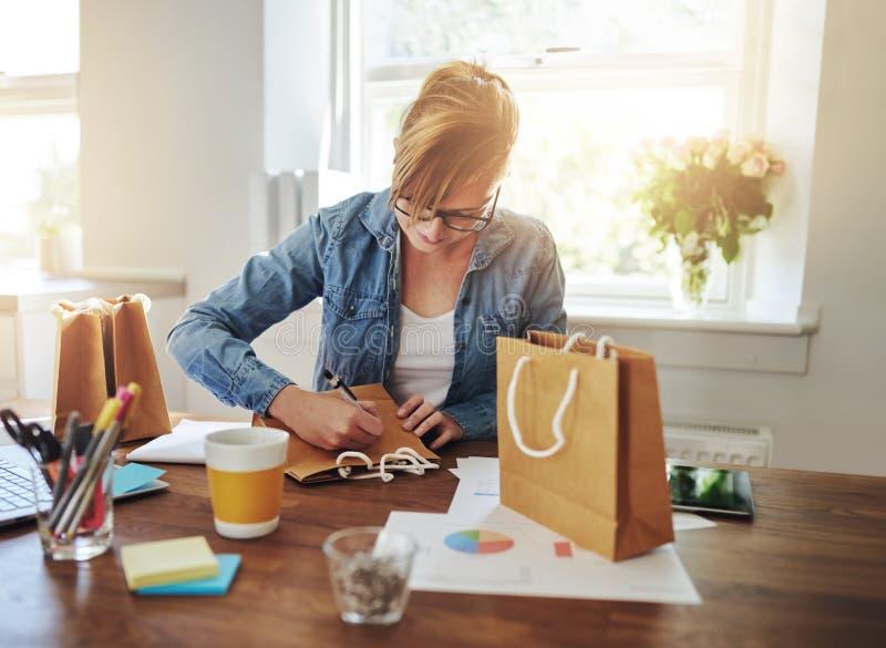 Молодая коммерсантка конструируя упаковку стоковые фотографии rf
