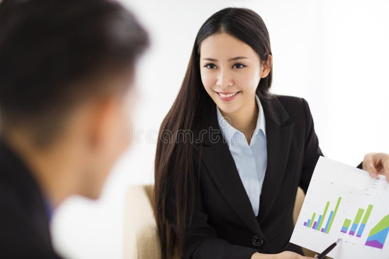 Молодая коммерсантка показывая диаграмму на диаграмме в офисе стоковые изображения