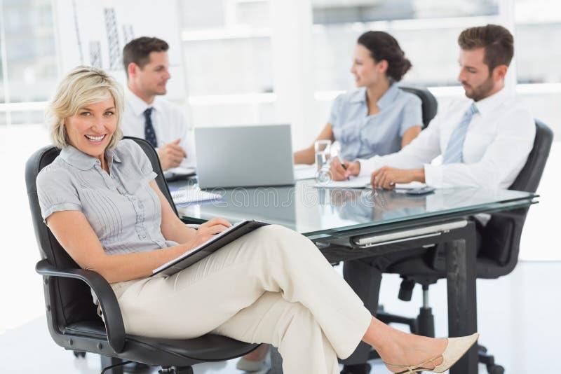 Молодая коммерсантка при коллеги обсуждая в офисе стоковая фотография
