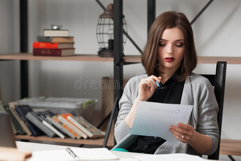 Молодая коммерсантка работая на бумагах дела стоковое изображение rf