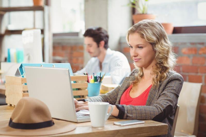 Молодая коммерсантка работая на компьтер-книжке в офисе стоковые фотографии rf