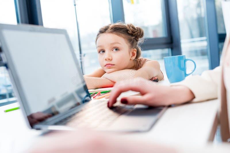 Молодая коммерсантка работая с компьтер-книжкой пока дочь смотря ее в офисе стоковое фото rf