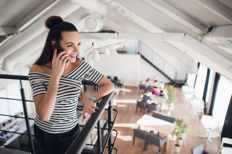 Молодая коммерсантка стоит в кафе и говорит на сотовом телефоне Девушка ждет друзей, коллег в ресторане стоковое изображение rf