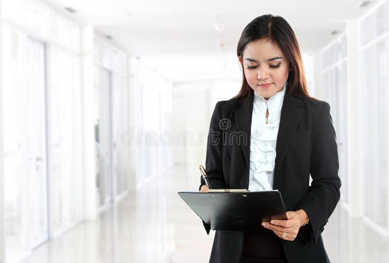 Молодая коммерсантка с доской сзажимом для бумаги стоковые фото