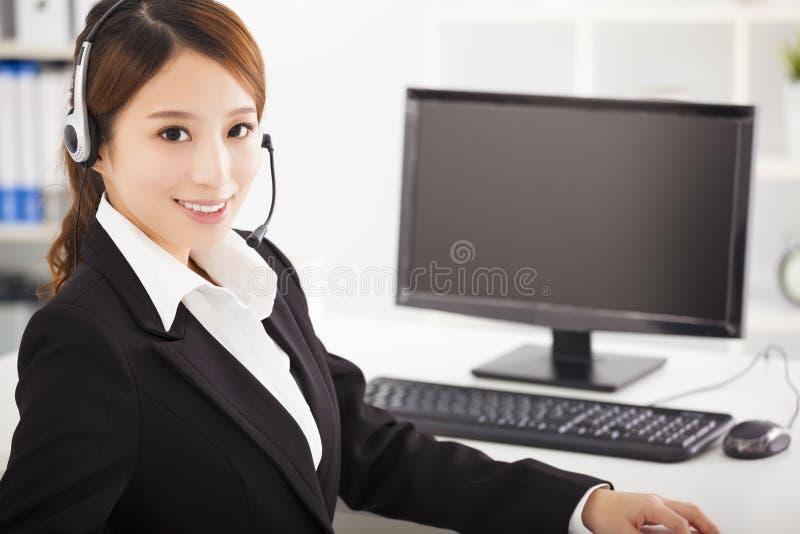 Молодая коммерсантка с шлемофоном в офисе стоковые изображения