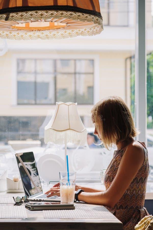 Молодая коротк-с волосами женщина используя компьтер-книжку в кафе стоковое изображение rf