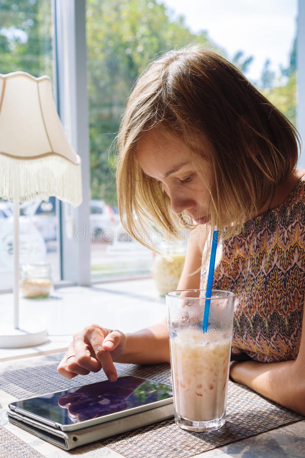 Молодая коротк-с волосами женщина используя таблетку в кафе стоковые фотографии rf