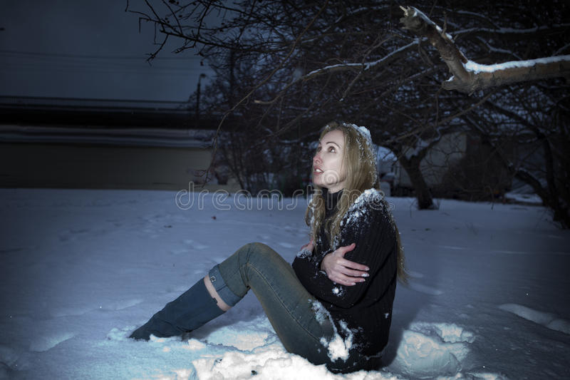 Молодая, который замерли женщина под падая снегом стоковые фотографии rf