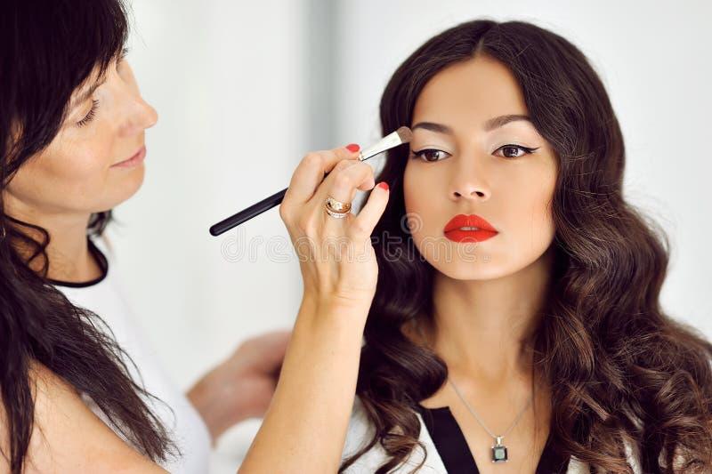 Молодая красивая азиатская женщина прикладывая состав художником состава стоковая фотография