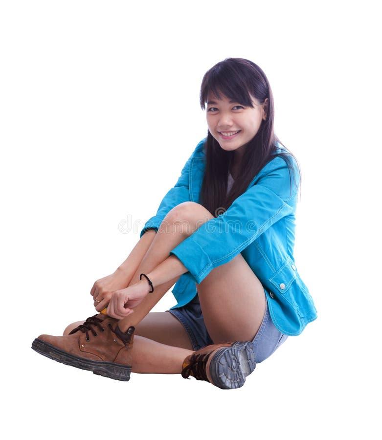 Молодая красивая азиатская женщина сидя и нося ее изолированные ботинки на белизне стоковые фотографии rf