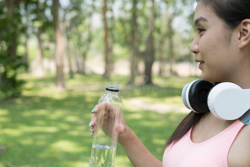 молодая красивая азиатская женщина спортсмена фитнеса держа выпивая wat стоковое изображение rf