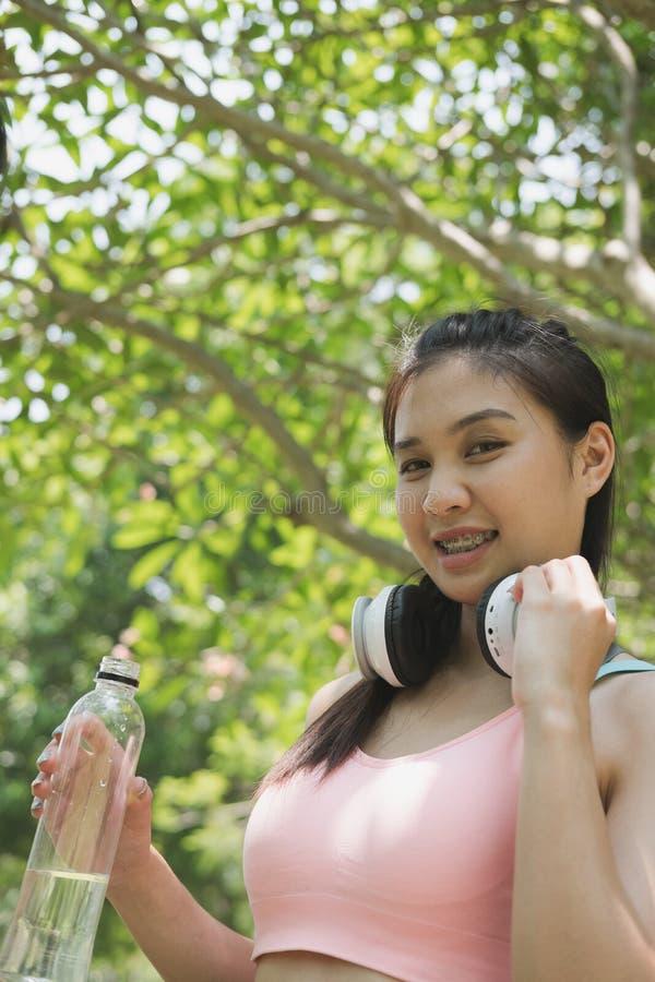 молодая красивая азиатская женщина спортсмена фитнеса держа выпивая wat стоковые фотографии rf