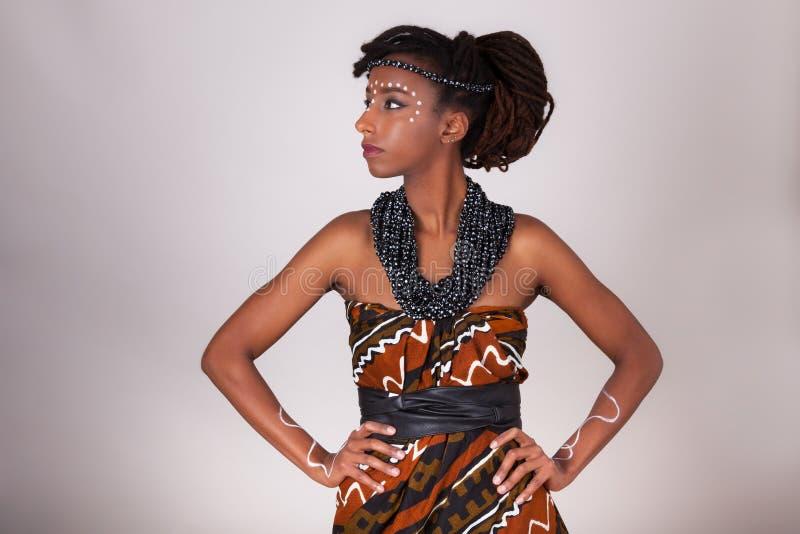 Молодая красивая африканская женщина нося традиционные одежды и j стоковое фото rf