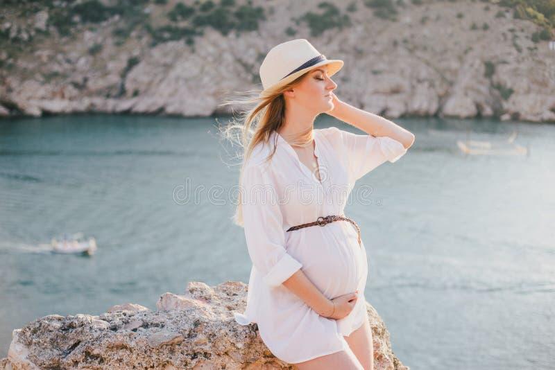 Молодая красивая беременная женщина представляя на горе около моря стоковое фото rf