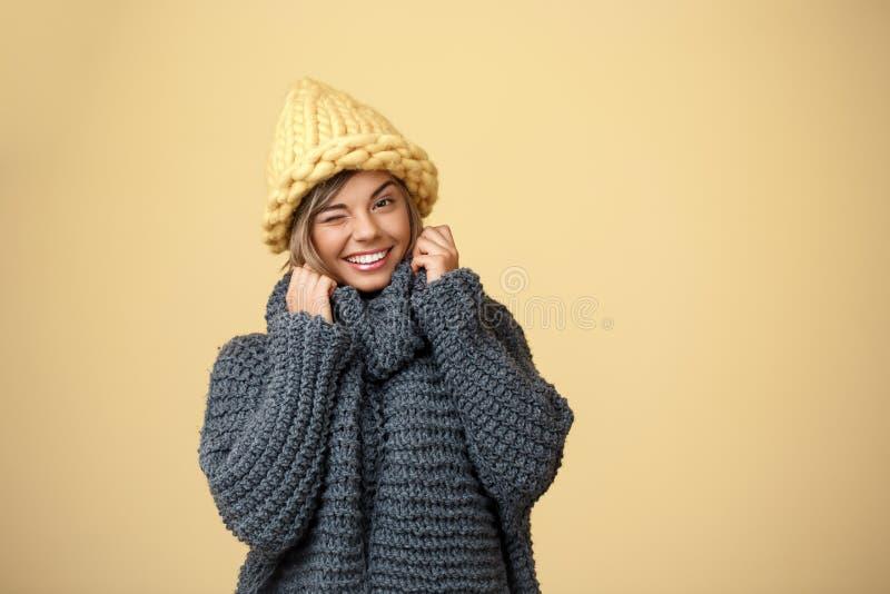 Молодая красивая белокурая девушка в knited подмигивать шляпы и свитера усмехаясь смотрящ камеру над желтой предпосылкой стоковые фото