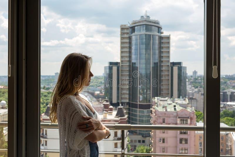 Молодая красивая белокурая девушка стоя на окне и унылая стоковое фото rf