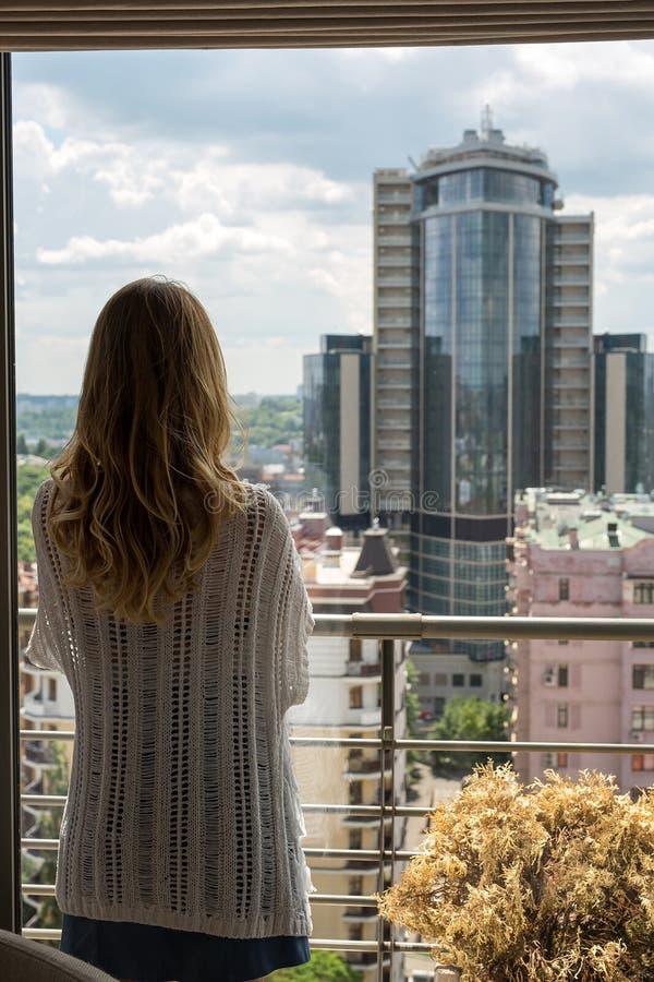 Молодая красивая белокурая девушка стоя с ей назад в окне и унылая стоковая фотография
