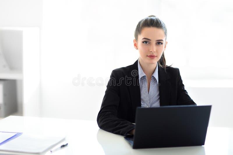 Молодая красивая бизнес-леди с компьтер-книжкой в офисе стоковая фотография rf