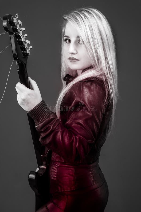 Молодая красивая блондинка с красным светом, электрической гитарой стоковая фотография rf