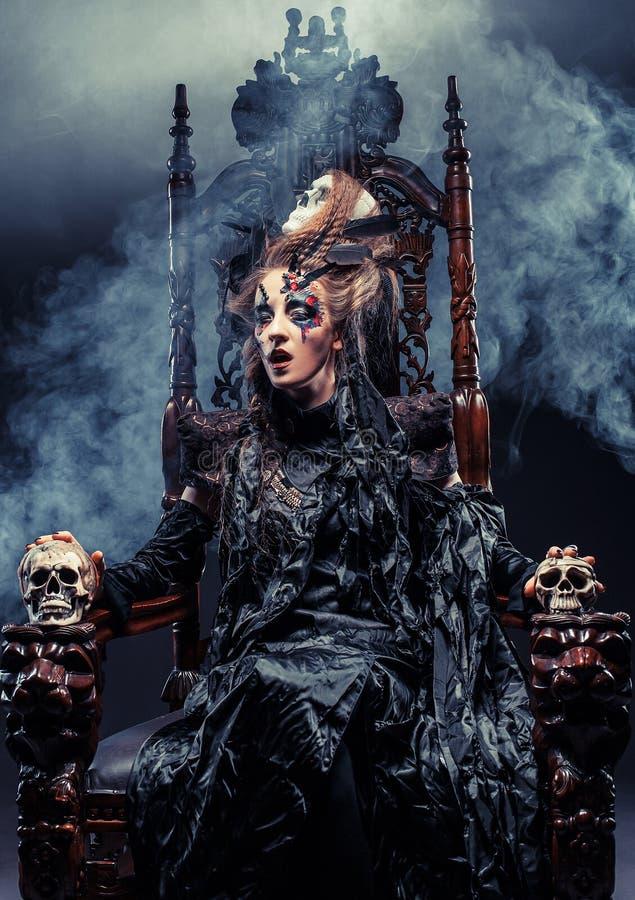 Молодая красивая ведьма сидит на стуле Яркий составьте, череп, тема хеллоуина дыма стоковое изображение rf