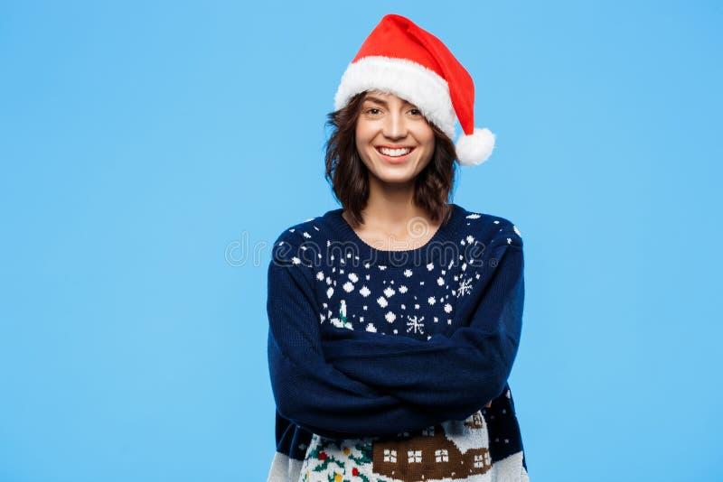 Молодая красивая девушка брюнет в knited шляпе свитера и рождества усмехаясь над голубой предпосылкой стоковые изображения rf