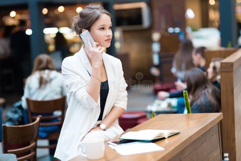 Молодая, красивая девушка в белом костюме, сидя в кафе на th стоковое изображение rf
