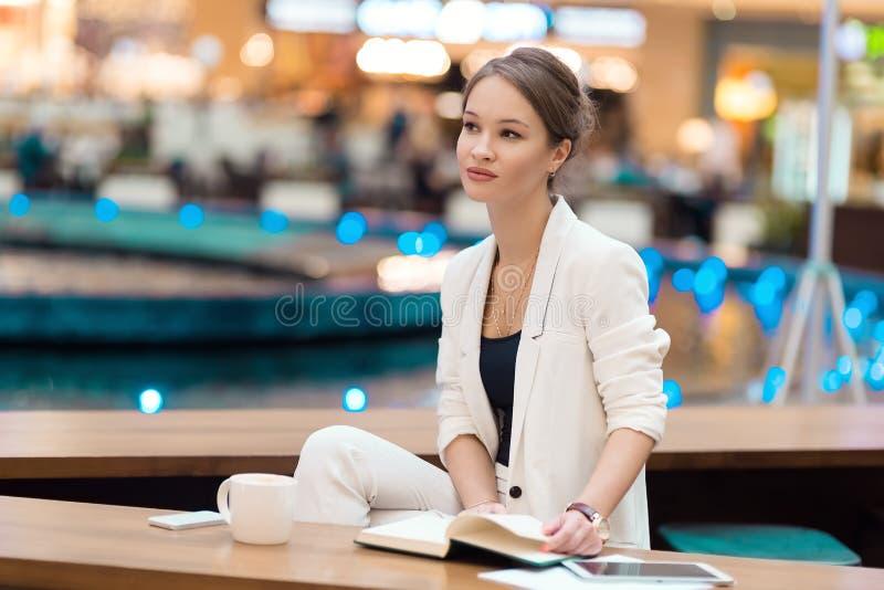 Молодая, красивая девушка в белом костюме, сидя в кафе на th стоковое фото