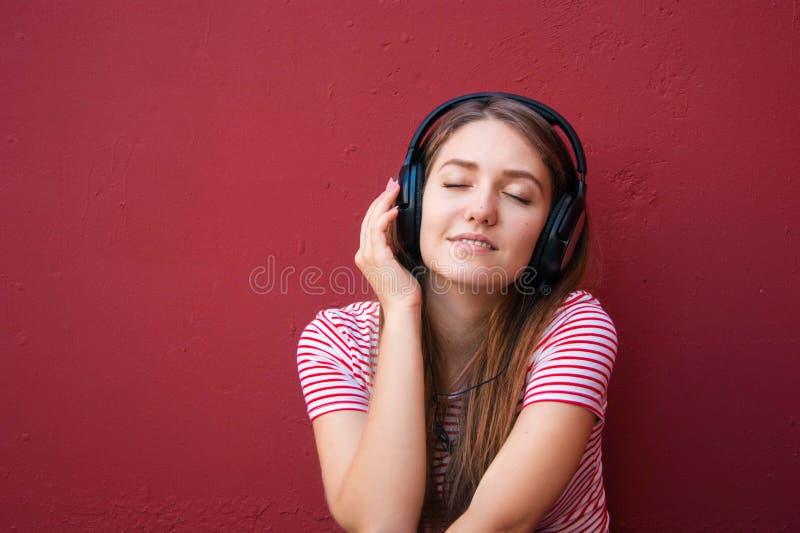 Молодая красивая девушка в наушниках слушая к музыке стоковые фотографии rf