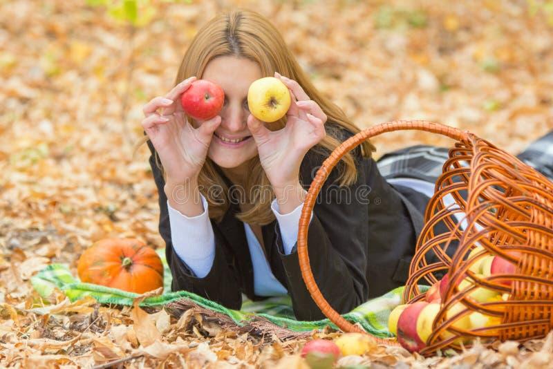 Молодая красивая девушка лежа на листьях в лесе осени в потехе и положенном яблокам к глазам стоковое фото rf